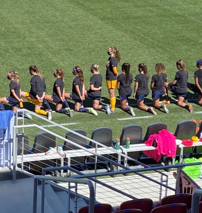 Lone woman soccer player standing for anthem